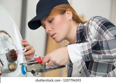 young female plumber working on water heater