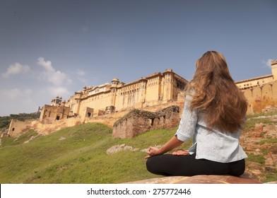 Young female practising yoga meditation at Amber fort, Jaipur, India
