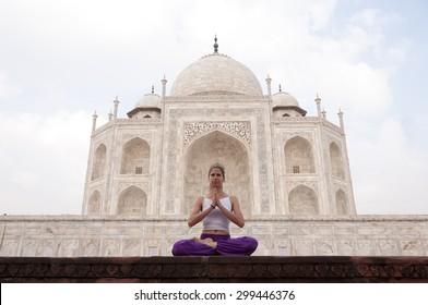 Young female practising yoga meditation at Taj Mahal, India
