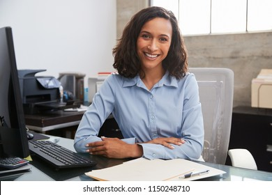 Young female professional at desk smiling to camera