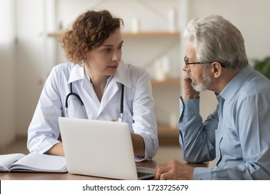 Young female professional doctor physician consulting old male patient, talking to senior adult man client at medical checkup visit. Geriatric diseases treatment. Elderly medical health care concept