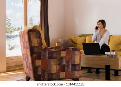 Young female professional is talking on her cell phone while freelancing in a beautiful mountain cottage