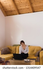 Young female professional is working on her laptop in a beautiful minimalistic mountain cottage