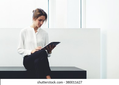 Young female proud ceo analyzing project on digital tablet while sitting in modern office interior, smart businesswoman using touch pad for learning new material before important meeting with clients