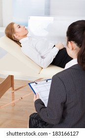 Young Female Psychiatrist Holding Clipboard Examining Businesswoman