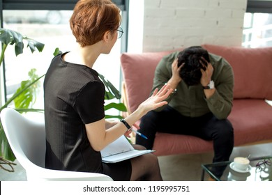 Young female psychologist working with indian man in modern office