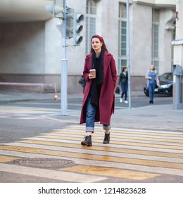 young female in purple coat with coffee cup cross the street crosswalk, square photo