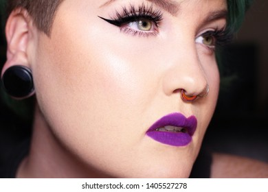 Young Female with Purple Lipstick, Winged Eyeliner and Long Lashes