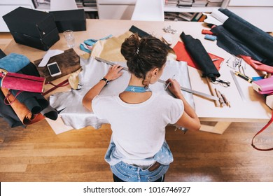 Young female purse maker working with leather textile at her workshop. Crafting tools on wooden table. Tailor, leather craftswoman wearing apron indoors