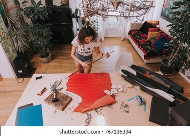 Young female purse maker working with leather textile at her workshop.Piece of red leather. Tailor,leather craftswoman making measurements. Crafting tools.Life is beautiful-print on t-shirt