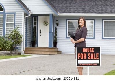 Young female real estate woman standing outside a house for sale.
