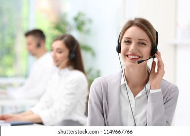 Young female receptionist with headset in office