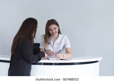young female receptionist at medical clinic or hospital discussing schedule with patient and writing record to the note book . She is smiling