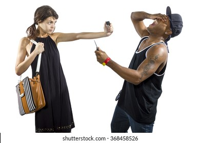 Young female refusing to be a victim of a criminal stealing her purse.  She is holding a pepper spray for self defense.