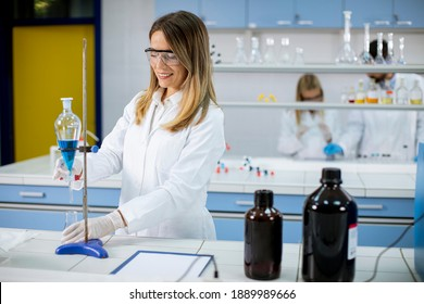 Young female researcher working with blue liquid at separatory funnel in the laboratory