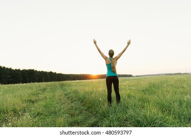 Young female resting after an active fitness training standing outdoor. Satisfied fit woman resting after an active fitness training