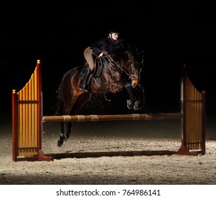 Young female rider on bay horse jumping over hurdle on equestrian sport training.Horseback riding.