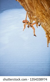 Young female rock climber in bikini hanging with one hand on overhanging cliff. On challenging climbing route over sea.