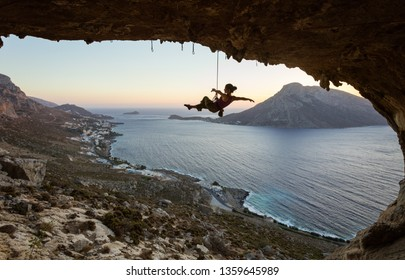 Young female rock climber hanging on rope and stretching out arms. Rock climber relaxing or fooling around while being lowered down against picturesque view at sunset.