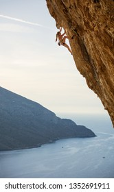 Young female rock climber on challenging route on cliff.