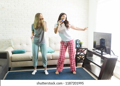Young female roommates singing and dancing during karaoke party at home