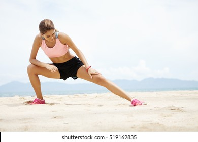 Young female runner with beautiful fit body warming-up her muscles before strength training cardio workout. Woman athlete in sportswear stretching legs with lunge hamstring stretch exercise on beach