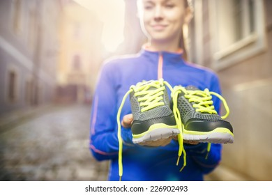 Young female runner carrying her running shoes in old city center