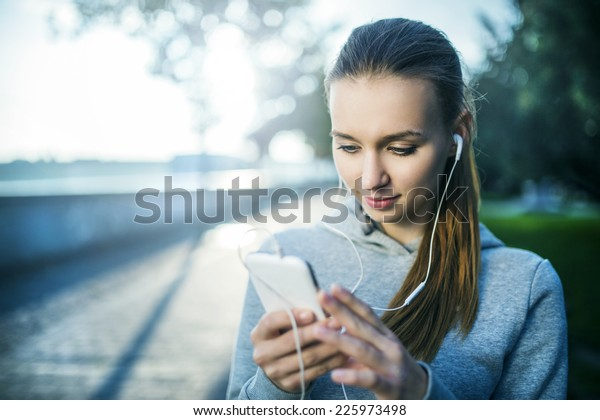 Young female runner is having break and listening to music during the run in city on a quay