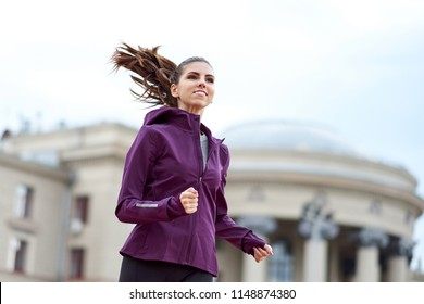 Young female runner in hoody is jogging in city street on background of an architectural building