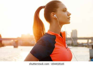 Young female runner jogging over sunset,river side,urban city copyspace