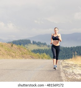 Young female runner on road cross in mountains. Slim smiling girl jogging in hillside