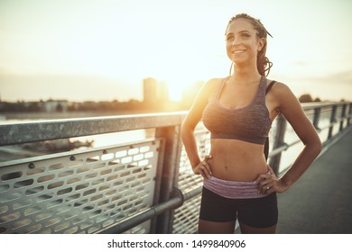 Young female runner is preparing to run and doing morning workout on a river bridge.