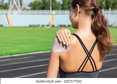 Young female runner standing and putting sun lotion on hand. Girl using sunscream before sport running exercise on summer morning. Sports and healthy concept.