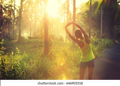 Young female runner stretching arms before running at morning forest trail