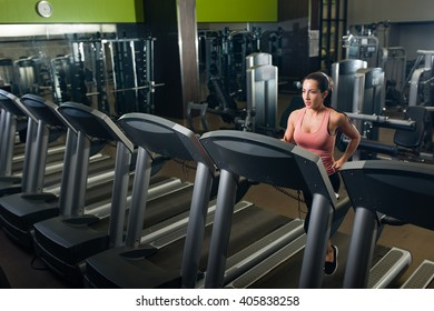 Young female running on a treadmill in a gym