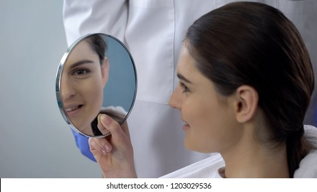 Young female satisfied with rhinoplasty result, smiling face reflected in mirror