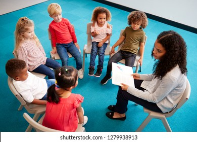 Young female school teacher reading a book to infant school children, sitting on chairs in a circle in the classroom listening, elevated view
