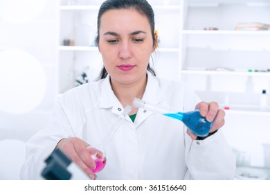 Young Female Scientist Analyzing Sample In Laboratory.laboratory assistant analyzing a sample.Toning image.