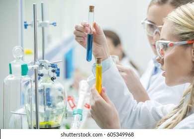 Young female scientists in protective glasses looking at test tubes with reagents in lab