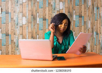 young female secretary sitting at her desk in her office going through some paperwork