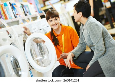 Young female seller assistant helps woman to choose washing machine in home appliance shopping mall supermarket