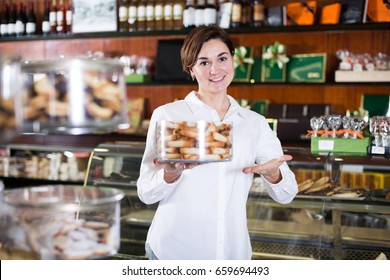 Young female seller offering tray of sweet rolls in confectionery
