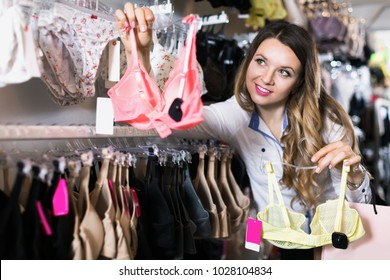 Young female shopper examining clothing in underwear shop