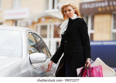 Young female shopper on a car parking