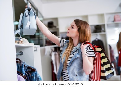 Young female shopper with shopping bags choosing the handbag matching her casual style