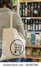 A young female shopper with a shopping cart logo canvas tote bag choosing products in a specialty grocery store.
