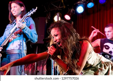 Young female singer performing on stage with band