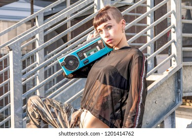 young female singer rap caucasian tattooed posing with a stereo radio on a metallic ladder