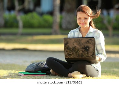 Young female sitting cross-legged on grass with laptop and books doing a homework
