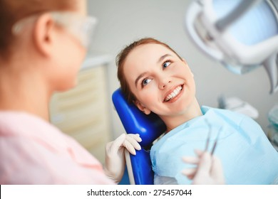 Young female sitting in dentist office and looking at her doctor with smile